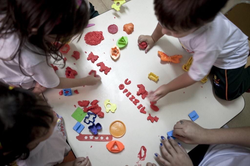 Crianças fazem atividade com massinhas em escola