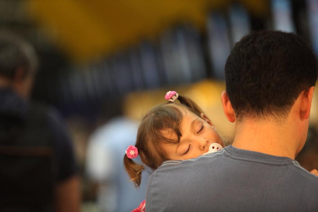 Pai com filha dormindo no colo em aeroporto lotado (Foto: Pierre Duarte - 20.abr.2011/Folhapress)