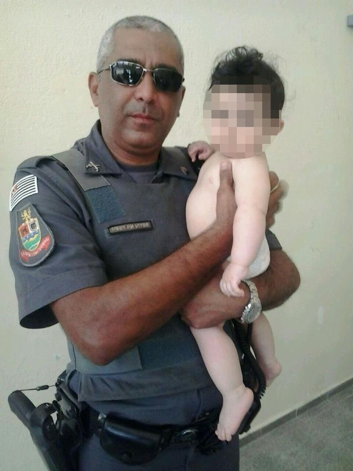 Bebê com policial após ter ficado 40 minutos preso em carro (Foto: Divulgação/PM)