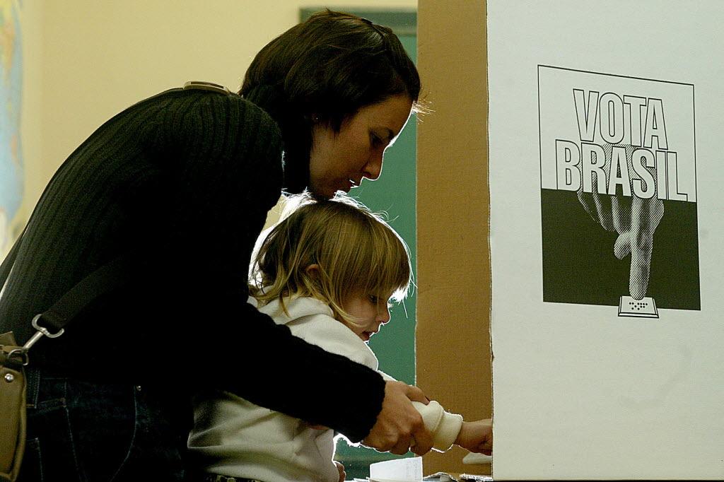 Criança ajuda mãe a votar durante eleição em São Paulo (Foto: Leonardo Wen - 01.out.2006/Folhapress)