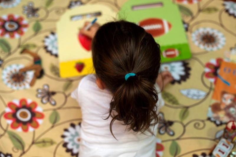 Criança lendo o livro que recebeu em casa escolhido de acordo com sua faixa etária (Foto: Divulgação)