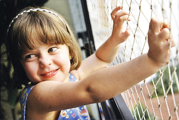 Mãe com filha pequena coloca rede para proteger janela (Luana Fischer -20.nov.2000/Folha Imagem)