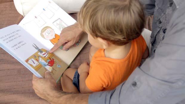 Criança lê um dos livros personalizados (Divulgação)
