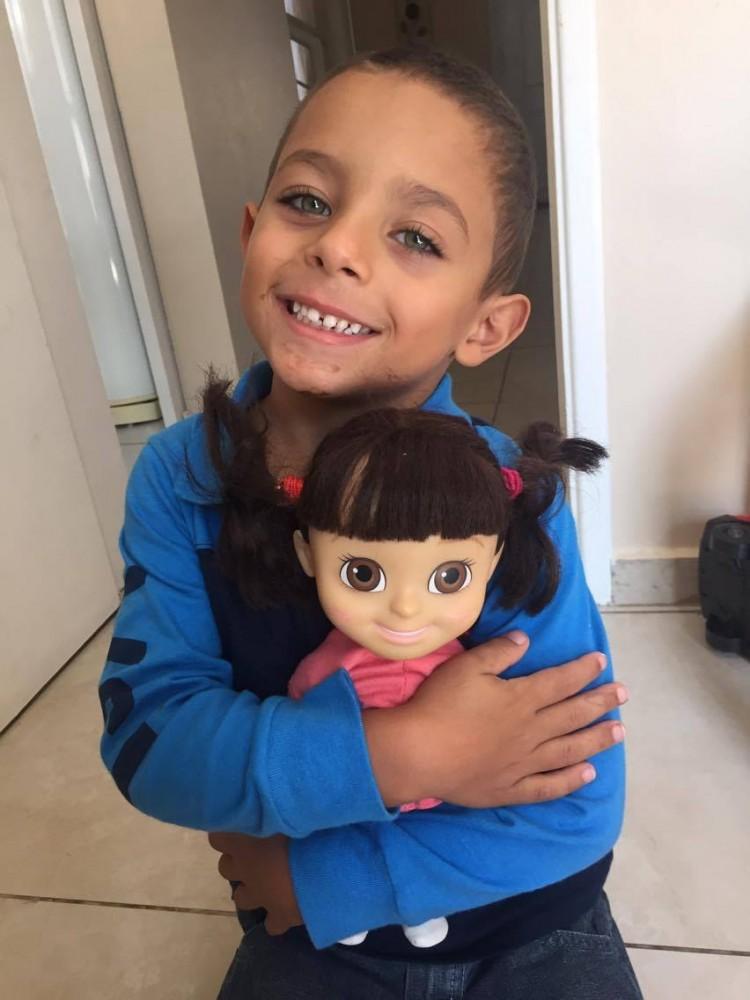 O filho de Fabíola segura a boneca que pediu para comprar (Reprodução/Facebook)