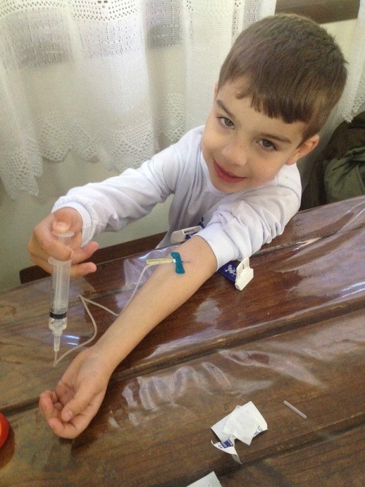 Criança fazendo auto-infusão domiciliar para tratamento profilático em hemofilia A grave (Arquivo Pessoal)