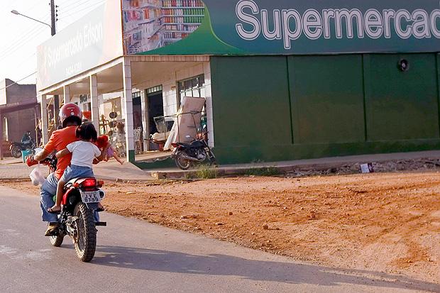 Motociclista trafega com criança na garupa sem capacete e com boneca na mão no sul do Pará (Foto: Apu Gomes/Folhapress)