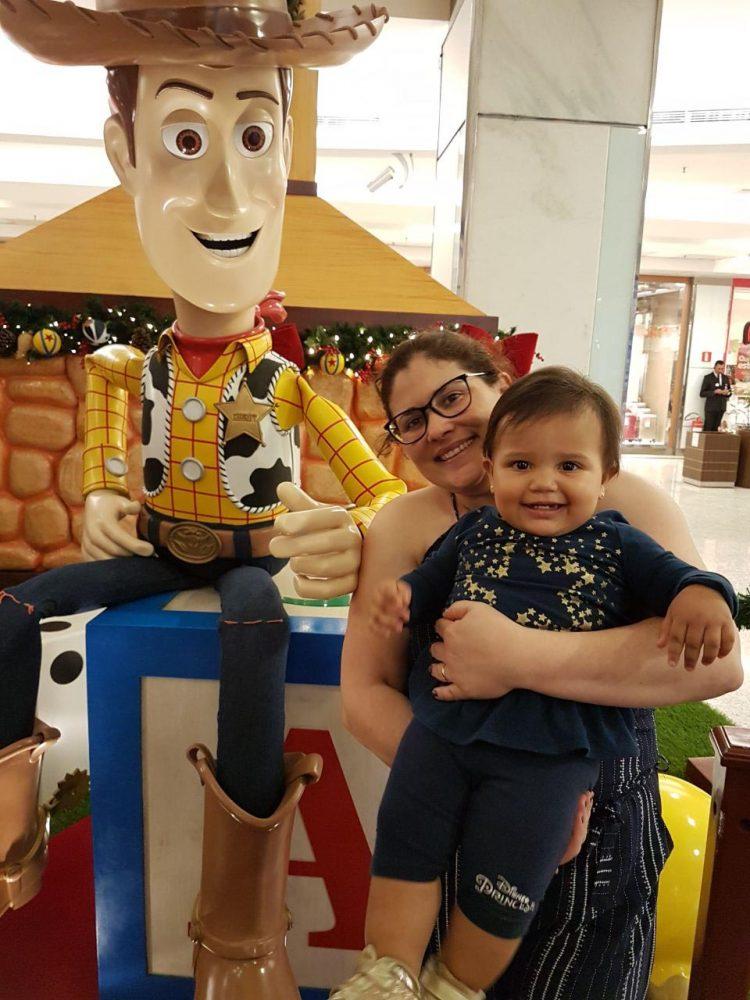 Juliana com a bebê no colo em frente ao personagem Woody, do Toy Story , em um shopping